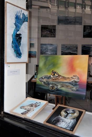 Une sélection des tableaux de l'artiste Evelyne Lair dans la vitrine de la galerie l'Art'monie